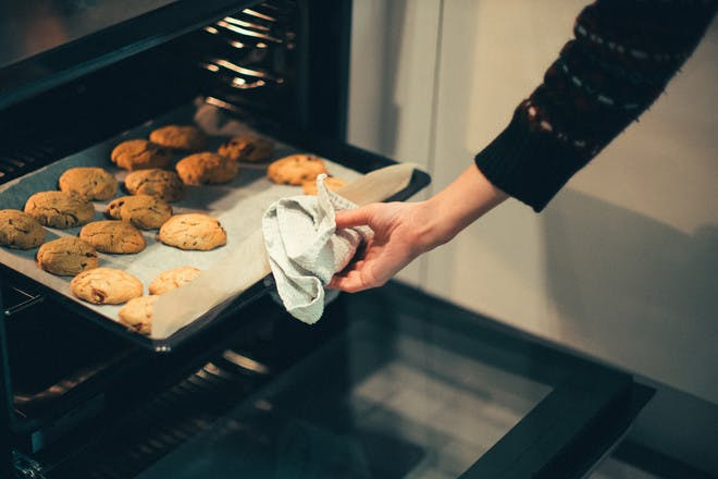 Hand taking biscuits out of oven