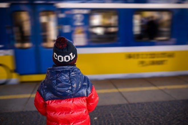 little boy watching train go past