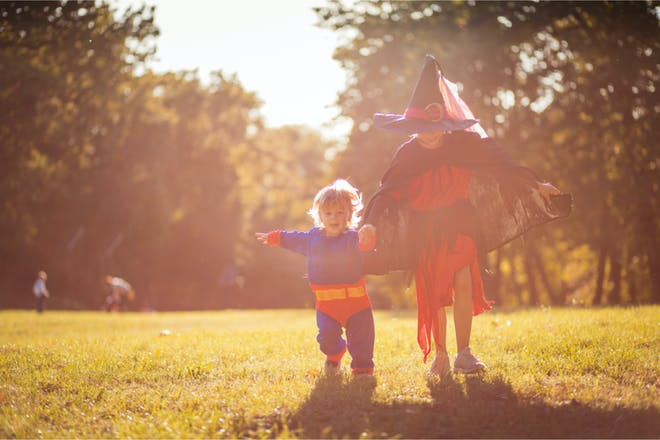 Two children dressed up in Halloween costumes running outside