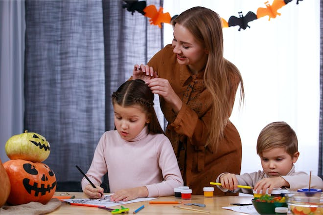 Mother doing her daughter's hair on Halloween
