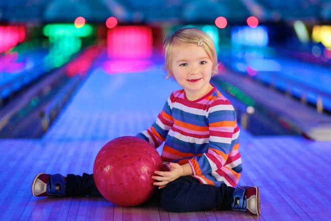 toddler holding bowling ball at bowling alley