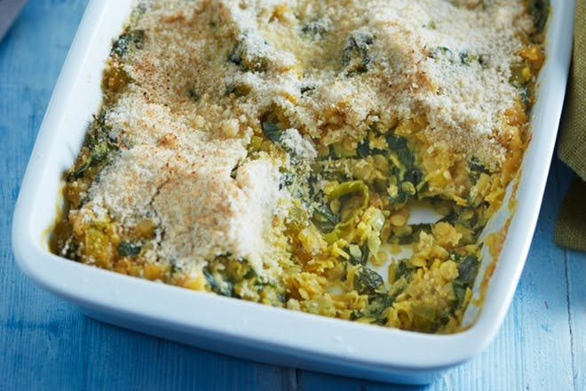 Lentil and spinach bake in a white tray with ground almond topping