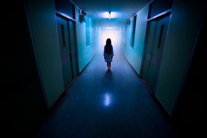 Child standing in dark hallway