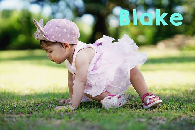 Baby on dress and baseball cap crawling on grass. Text says Blake