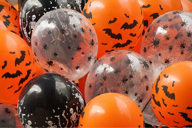 Halloween party balloons in orange, white and black decorated with spiders, bats and skeletons