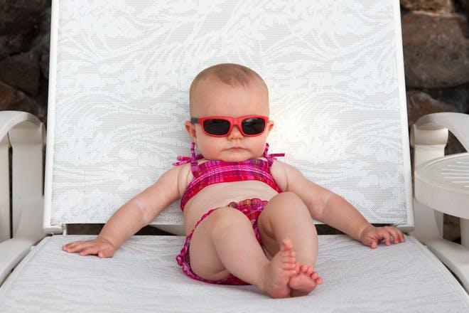 Baby wearing sunglasses on sun lounger
