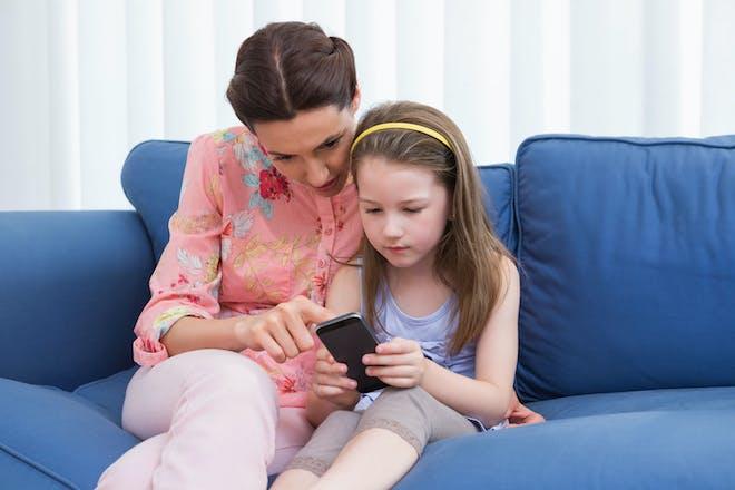 Girl and mum looking at phone on sofa