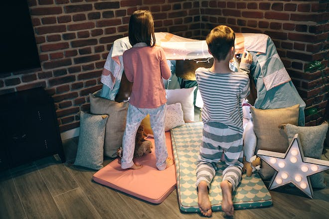 Boy and girl making a den in living room for a sleepover