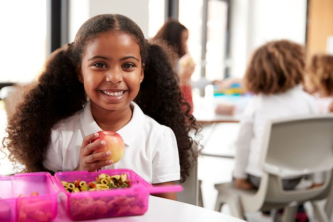Child in school uniform with pink lunch box smiling and holding apple