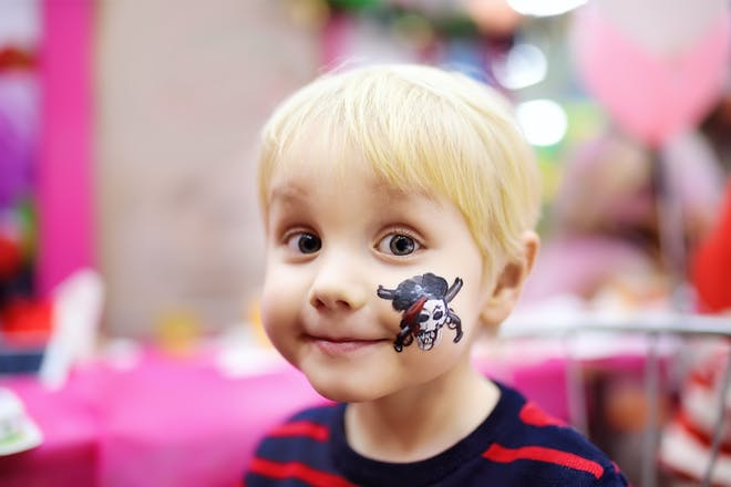 Toddler getting face painted with a skull and cross bones for Halloween
