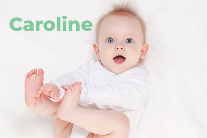 Red headed baby holding feet. Name Caroline written in text