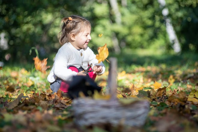 A toddler plays in the autumn leaves near her witch's hat and basket