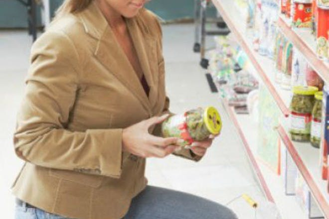 woman holding jar in shop