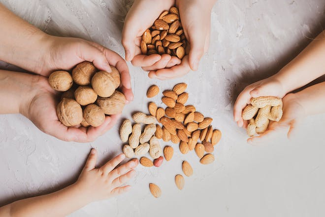 Adult and children's hands holding different types of nuts