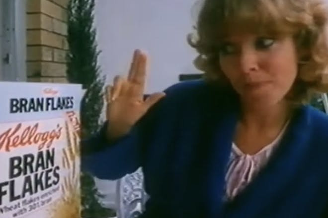 Woman looks at a box of breakfast cereal in an old TV advert for Bran Flakes