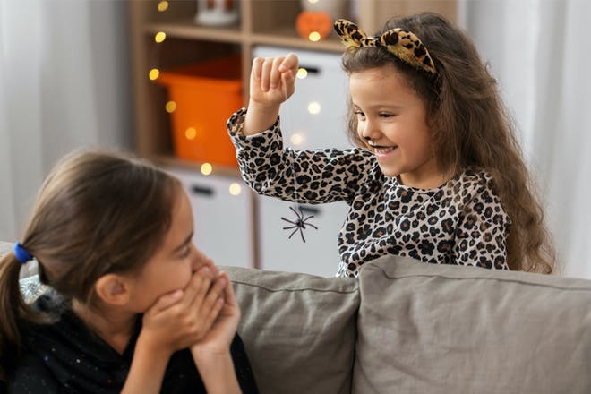 Little girl scaring her friend with a spider on Halloween