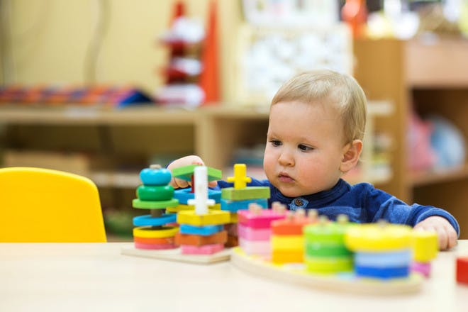 Toddler playing – stacking coloured shapes