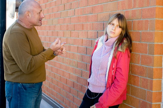 Dad lecturing teen daughter who looks annoyed