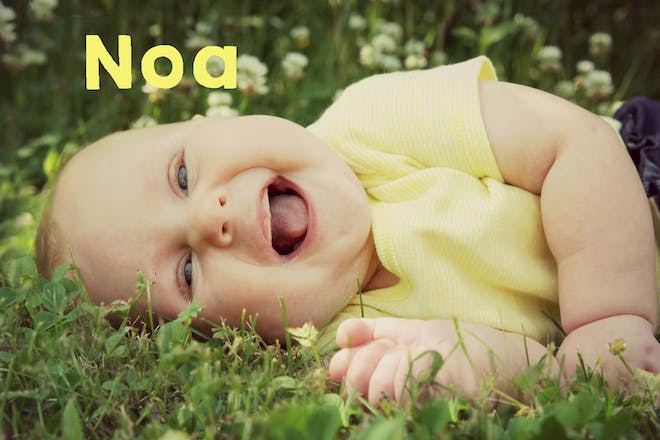 Baby lying on grass and laughing. Text says Noa