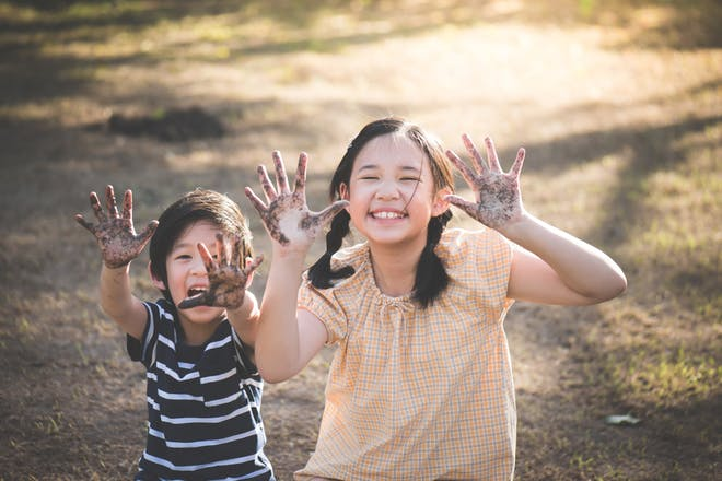 smiling children with muddy hands