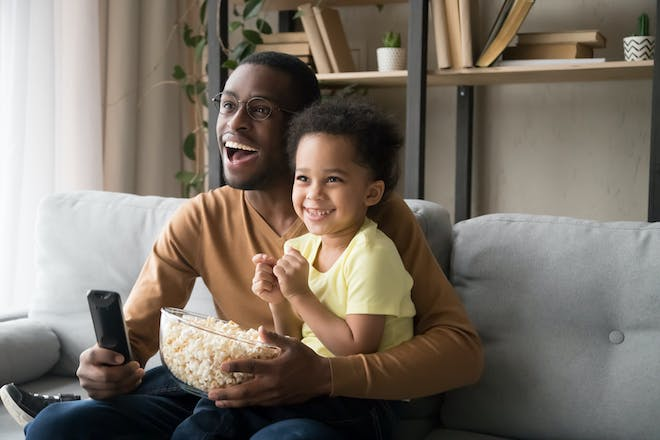 father and son watching movie and eating popcorn