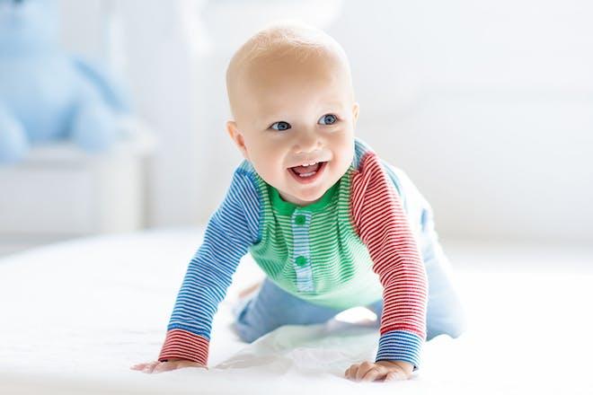 Crawling baby in striped babygro