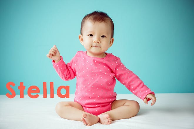 Baby in a pink babygrow sitting before a blue background