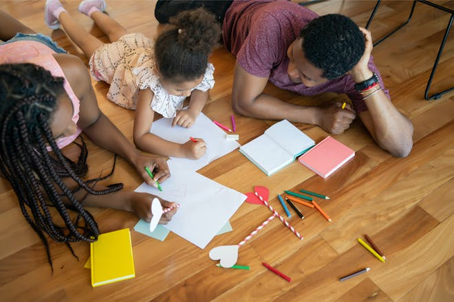 Parents and child writing and drawing at home