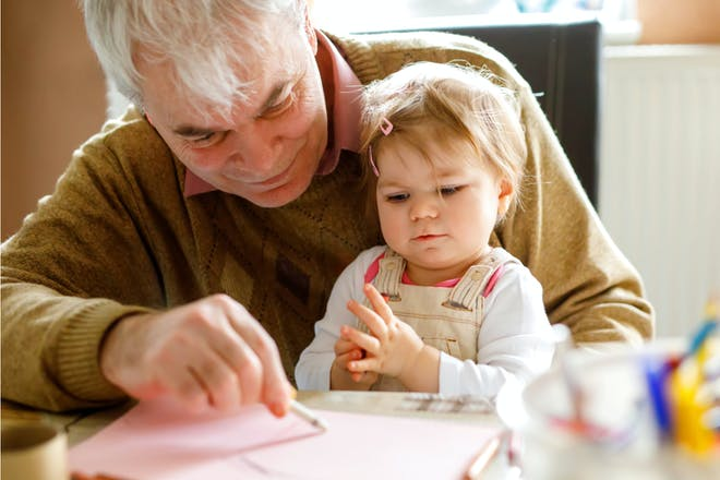 Grandparent helps toddler with crayon craft activity