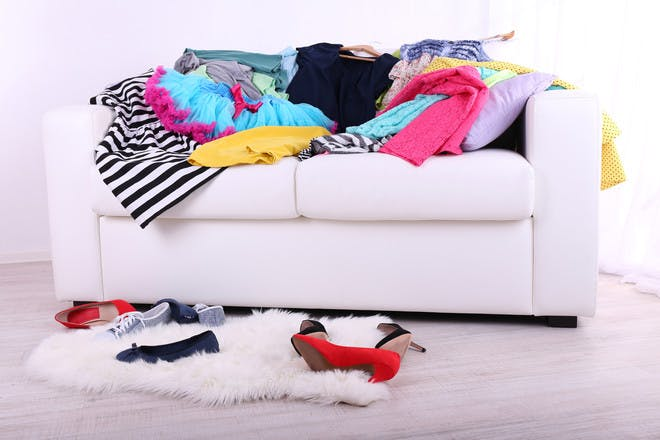 Sofa covered in clothes