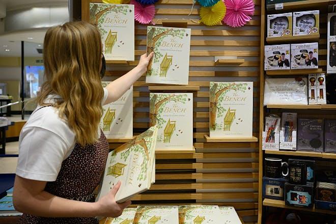 Shop assistant puts books on shelf