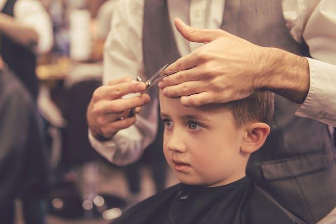 Young boy having his hair cut at barbers