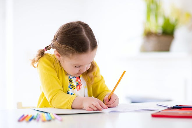 Little girl writing in book with coloured pens