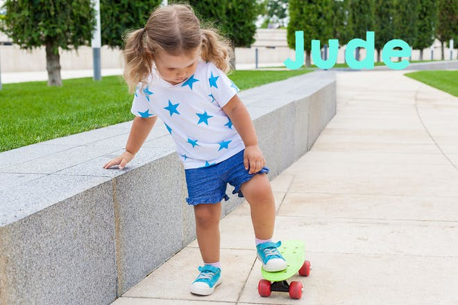 Toddler girl on a skateboard. Text says Jude