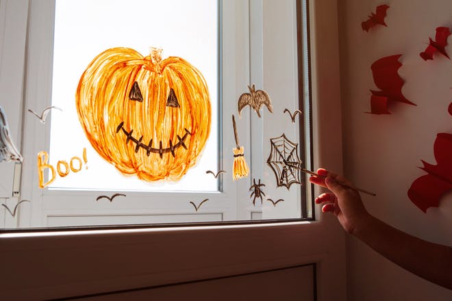 Picture of Halloween pumpkin, broomstick, spider's web and bats painted onto window