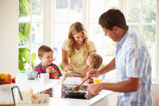 Dad cooking while mum entertains kids in kitchen