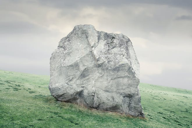 Large standing rock on grassy slope