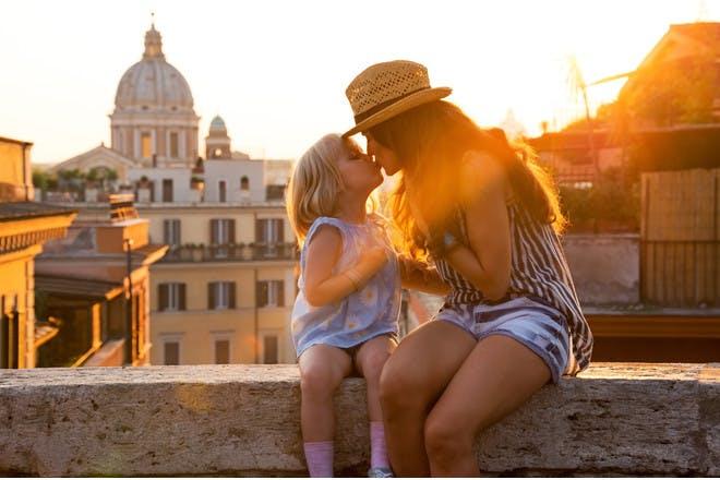 mum and daughter kissing at city sunset
