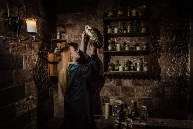 Girl holding owl in magic themed escape room