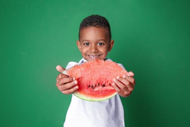 boy holding a slice of watermelon