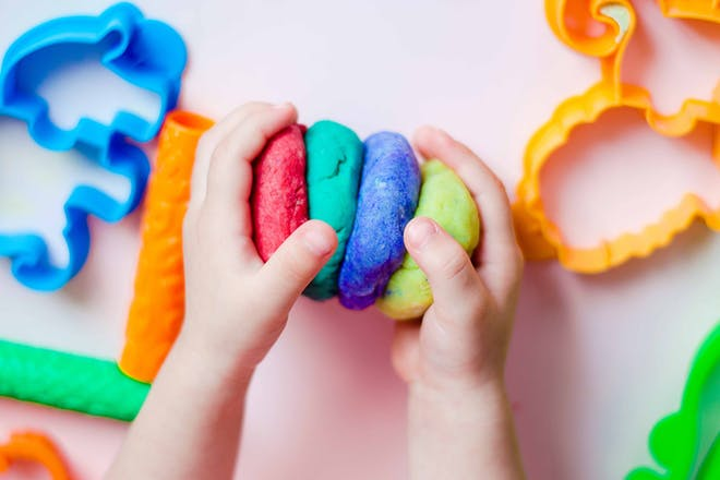 Child playing with red, green and blue playdough