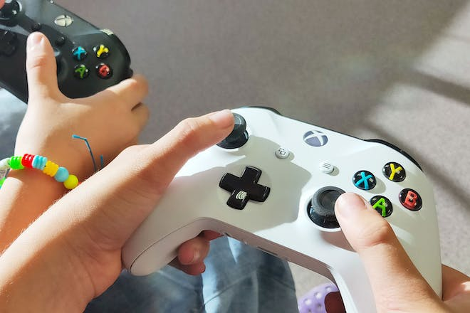 teenager and child playing with xBox controllers