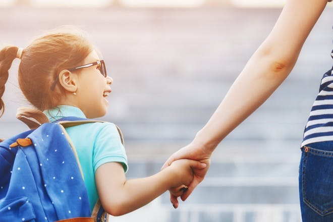 Child holding mum's hand on first day of school