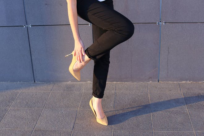 Lady wearing black trousers and yellow heels