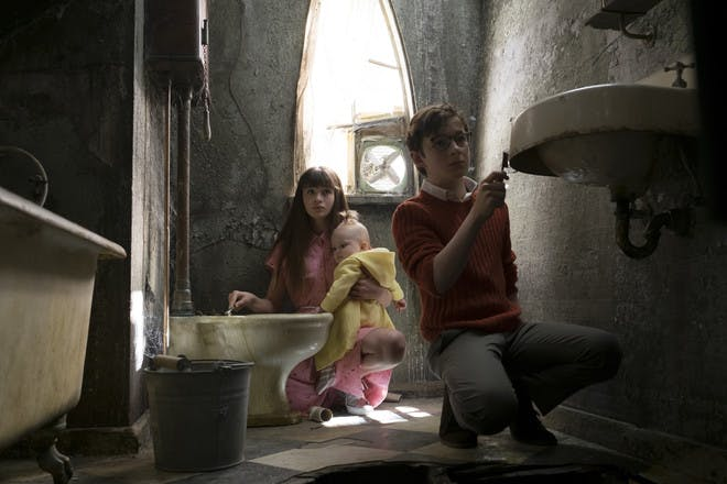 production still from Netflix A Series of Unfortunate Events - the Baudelaire children cleaning a bathroom