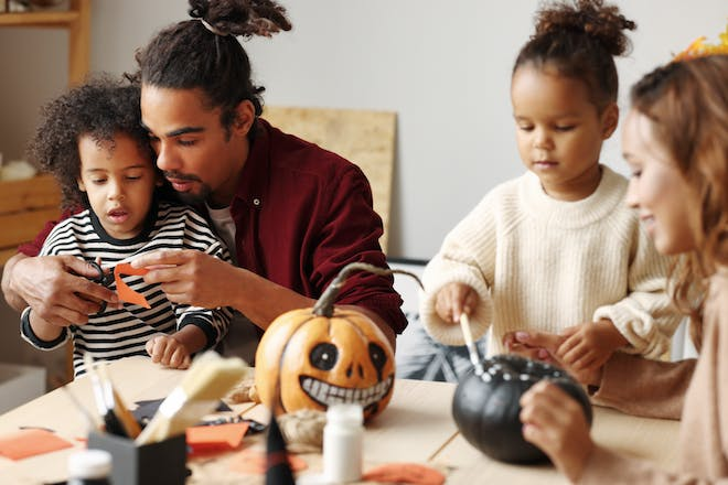 Family painting pumpkins and making Halloween crafts