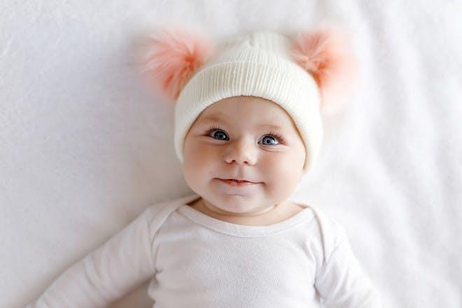 Baby girl with pink pom pom hat