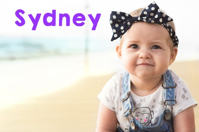 Baby girl with dungarees and hair bow on beach. Text says Sydney