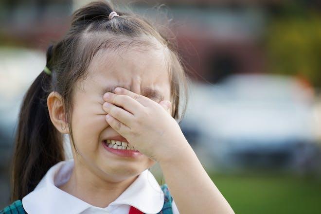 Young girl crying wearing school uniform