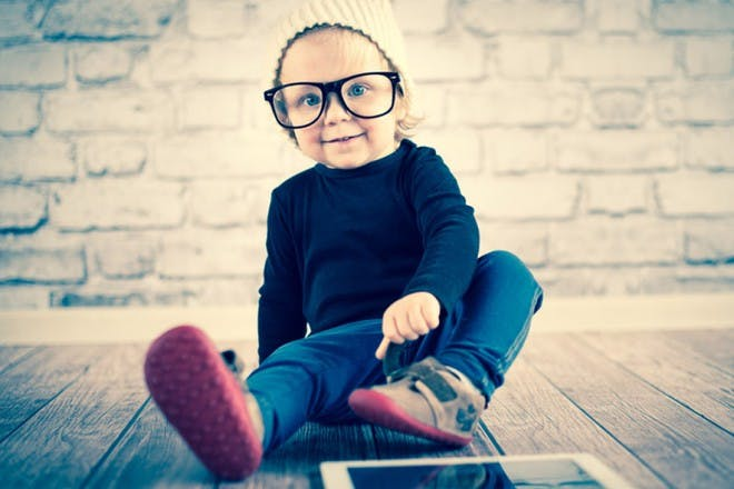 little boy with glasses and ipad